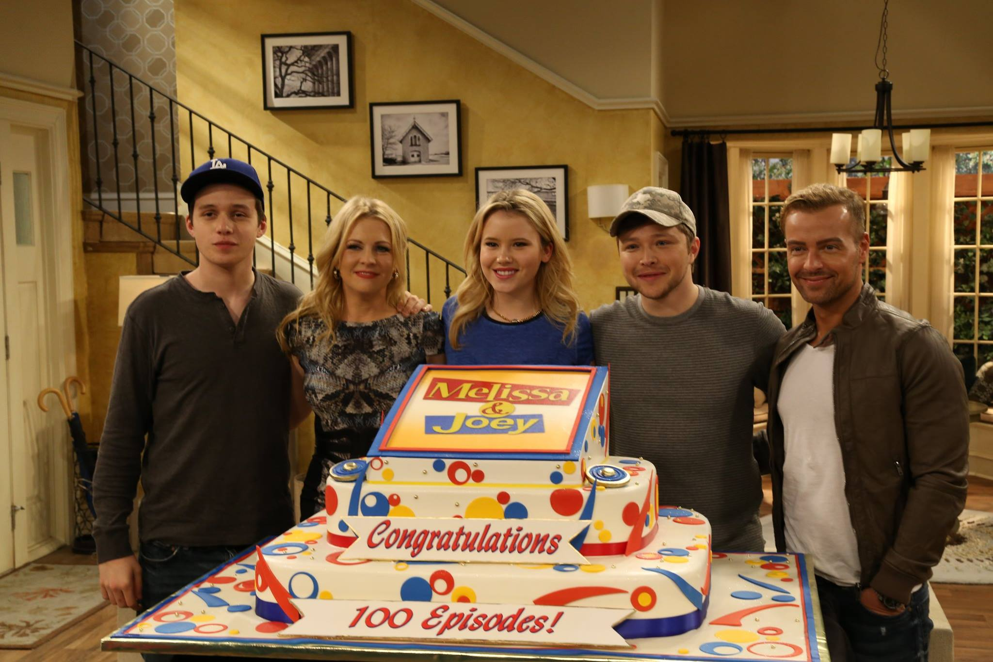 The cast of Melissa and Joey celebrates their 100th episode. Photo from Facebook. Photographs by Keith Dotson can be seen on the stairs.