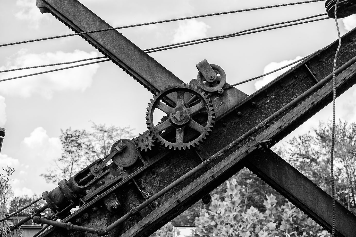 The rails and gears of a rusty steam shovel, found abandoned in a rural pasture.