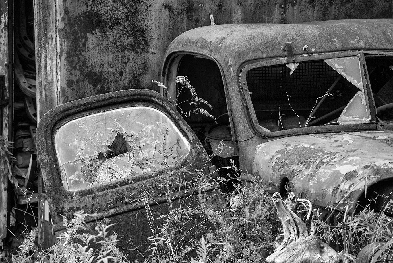 Broken windows on a rusty antique truck, abandoned in an overgrown meadow.