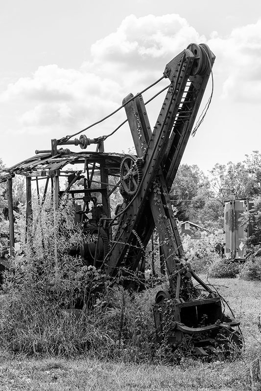 The bones of a rusty, antique steam shovel in a rural meadow.