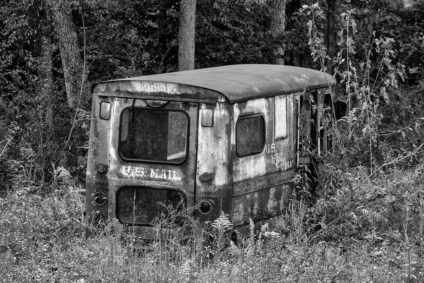 Abandoned mail carrier vehicle abandoned in an overgrown field, still showing its faded US Mail markings.