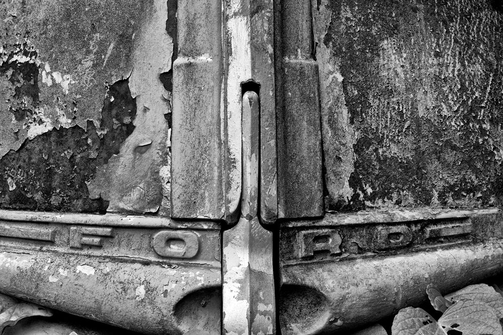 Ford emblem on the front of an abandoned antique truck