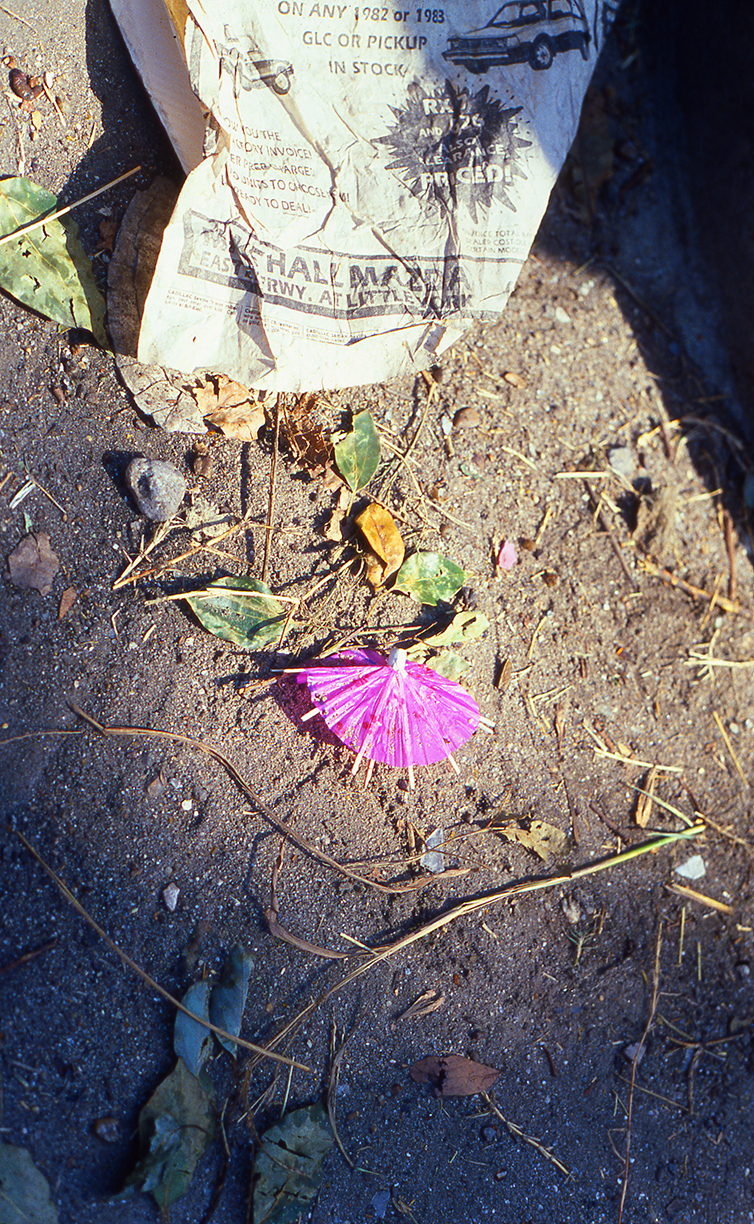 Tiny pink umbrella and newspaper in the dirt at the Westheimer Street Festival in Houston, early 1980s, shot on slide film by Keith Dotson. All rights reserved.