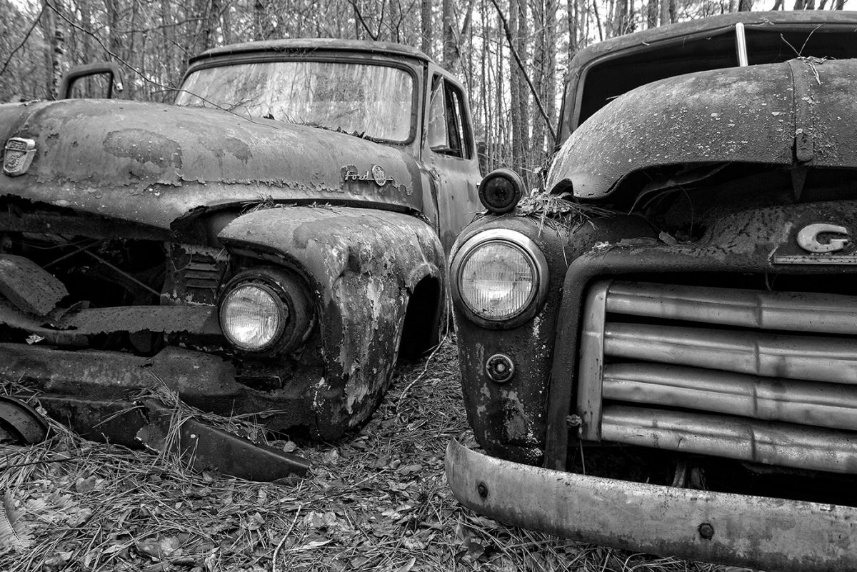 Black and white photograph of two rusty trucks in the woods of northern Georgia, by fine art photographer Keith Dotson.