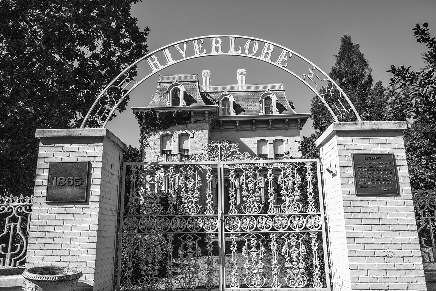 Riverlore Mansion seen behind its arched and ornamental iron gates.