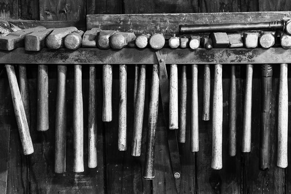 Row of hammers in a working blacksmith shop. Black and white photograph by Keith Dotson.