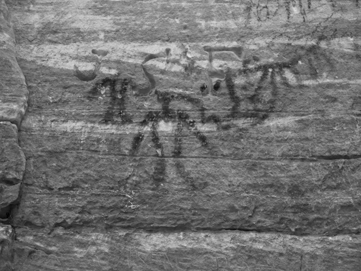 In grayscale, the Native American petroglyphs are more visible, adjacent to other damage.