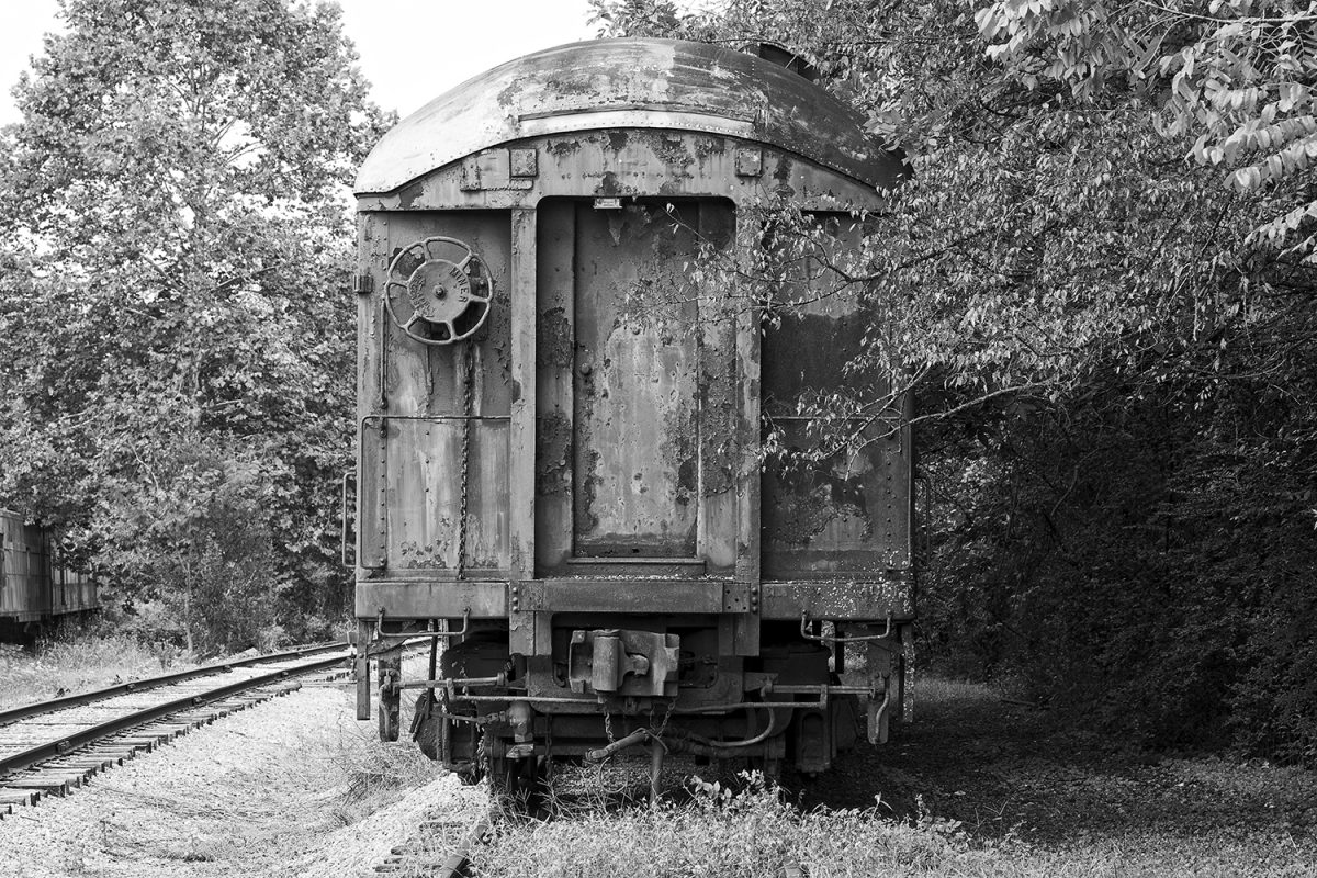 Black and white photograph of a rusty train car by Keith Dotson