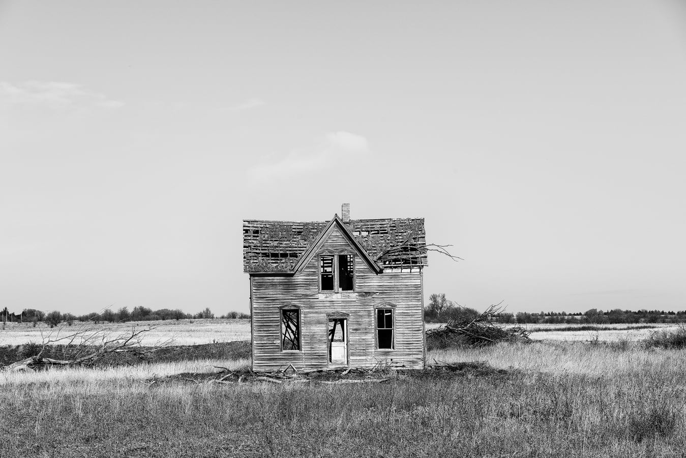 Black and white photograph of an abandoned farm house on the Kansas prairie