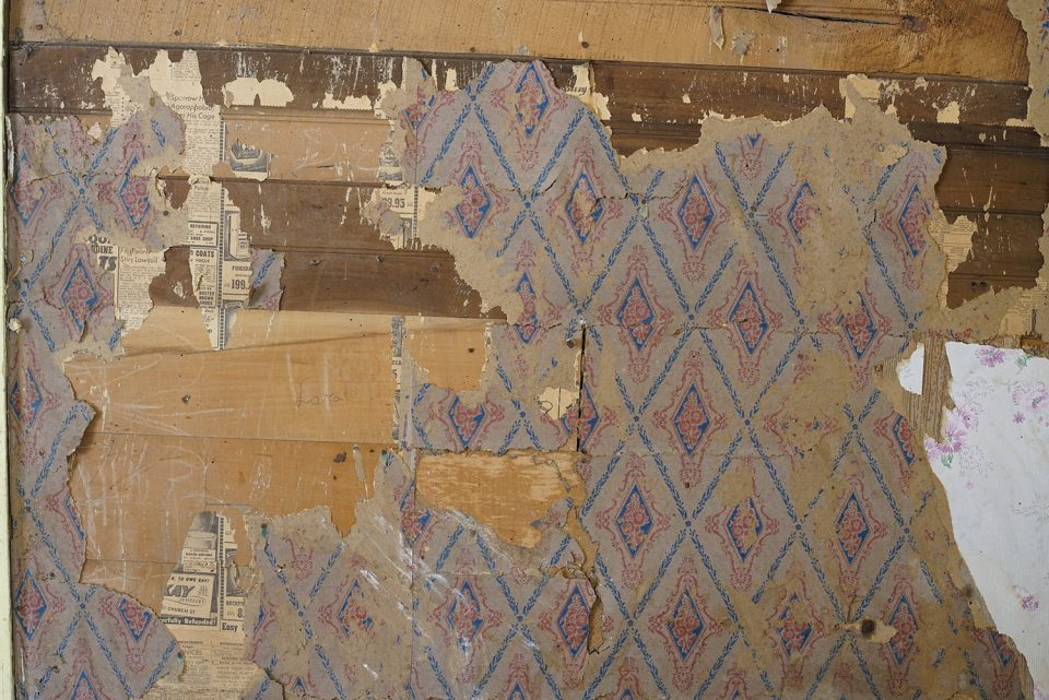 Wallpaper on the walls of an old farmhouse, Note the scraps of newspaper beneath the wallpaper.