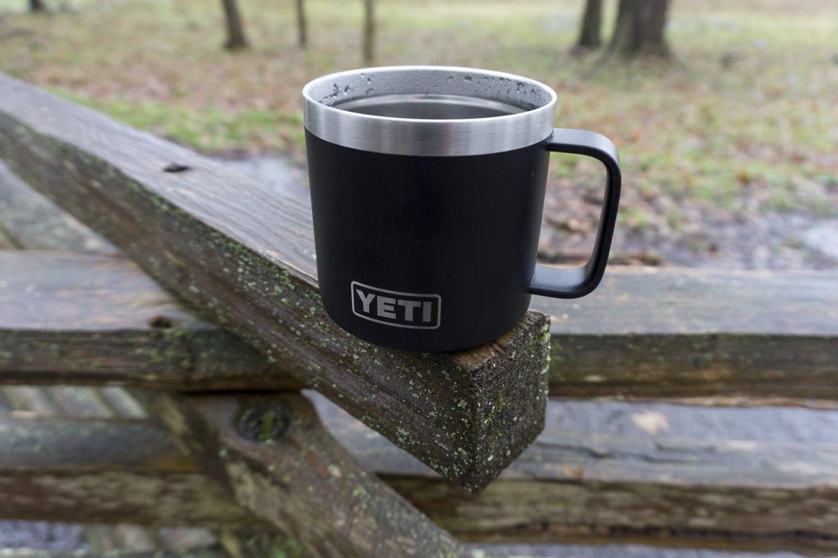 Picture of a black Yeti mug on a split rail fence on a rainy day
