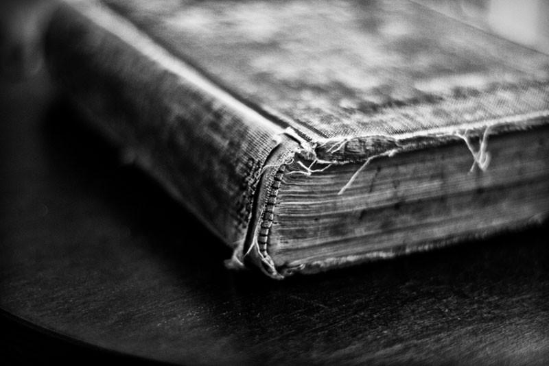 Black and white photograph of a tattered old history book, filled with the handwritten notes of Iva Carter, circa 1921.