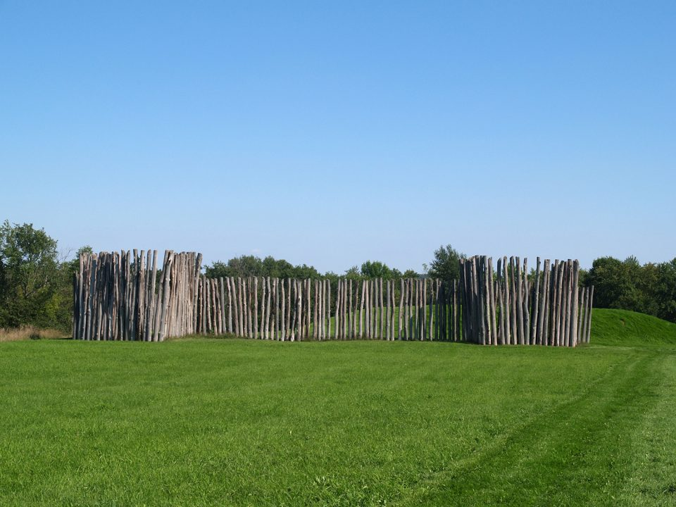 This photograph depicts part of Aztalan's reconstructed palisade, with a mound visible behind. With the manicured green grass, it's an appealing park in springtime.