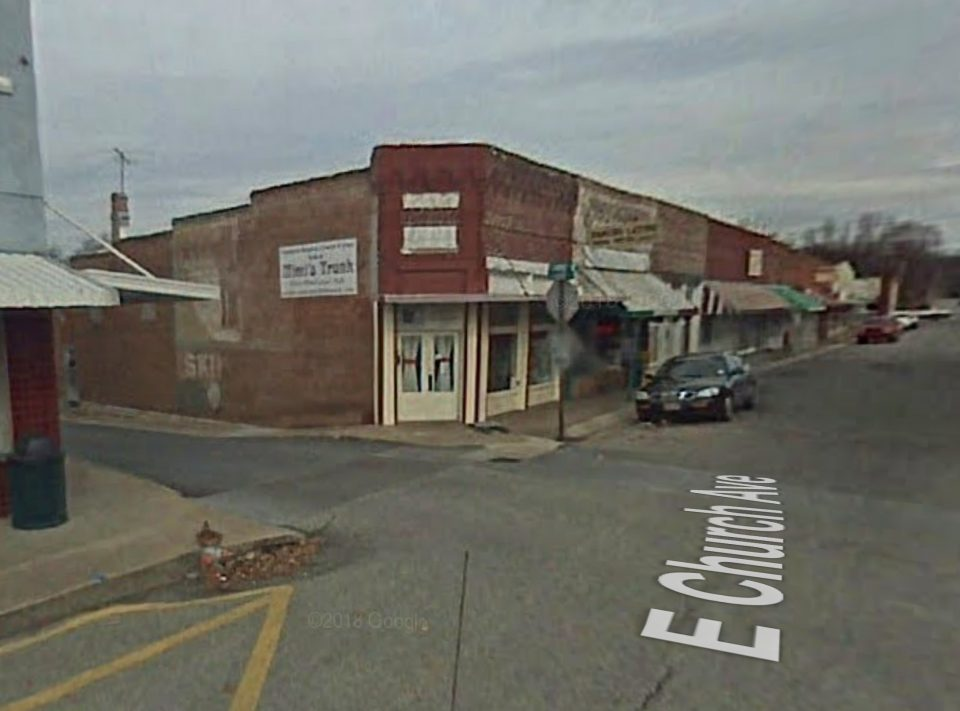 This Google Street View of the location was captured in 2008. It shows the serious deterioration of the wall signs on the side of Skip's Barber Shoppe.