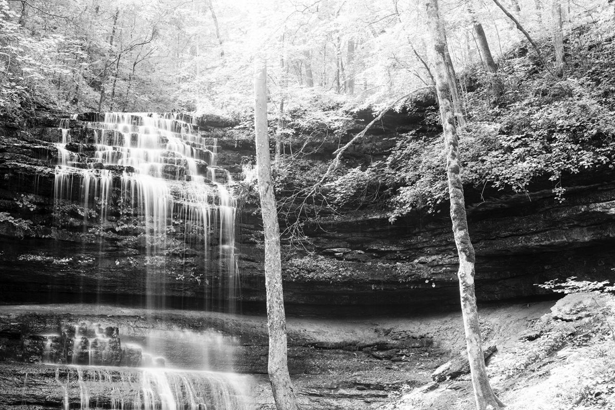 Black and white photograph of a sunlit waterfall by Keith Dotson.