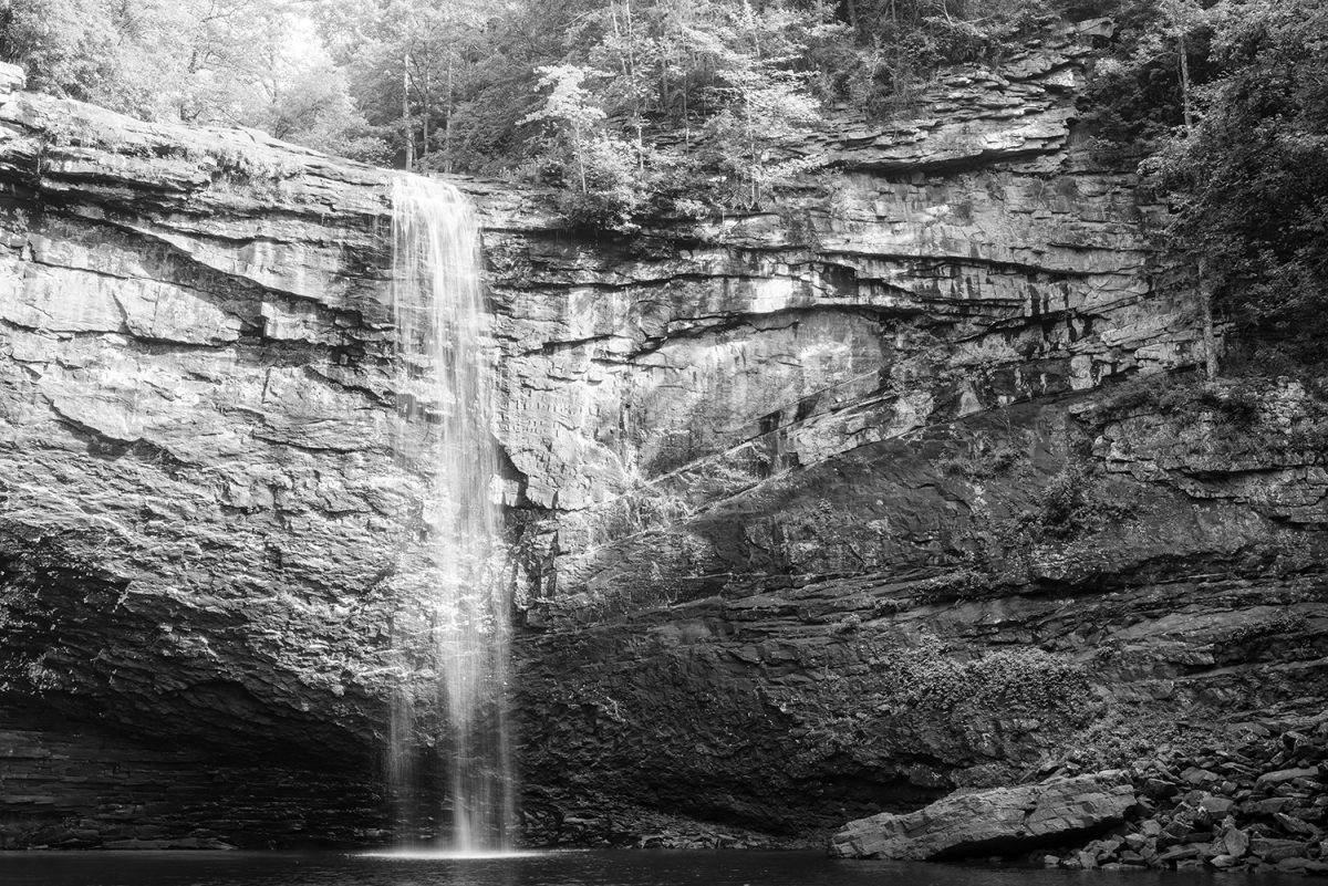 Black and white photograph of a 60-foot waterfall plunging into a deep pool, by Keith Dotson.