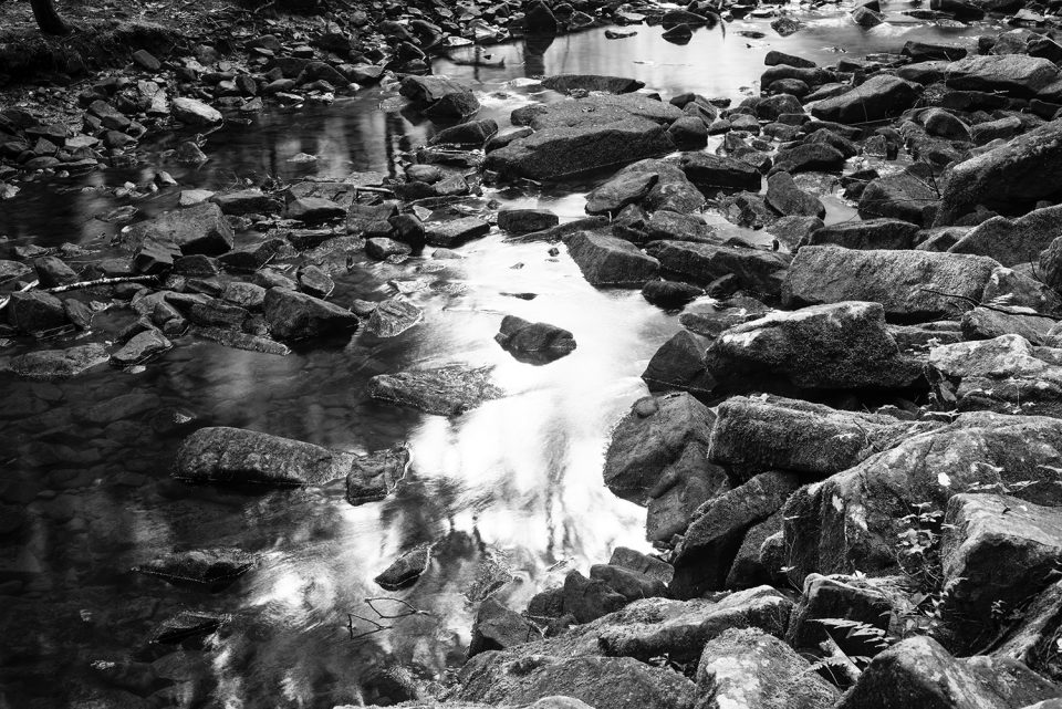 Black and white photograph of a rocky stream below the waterfall by Keith Dotson.