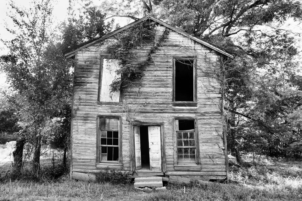 Black and white photograph of an abandoned building in Rodney, Mississippi. This building may have been a saloon, or a house, or a Masonic Lodge (or all three).