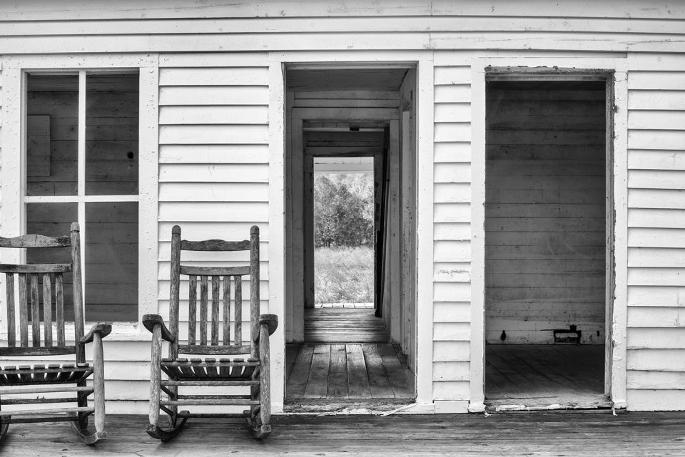 Looking through three doors of an empty farmhouse. Black and white photograph by Keith Dotson.