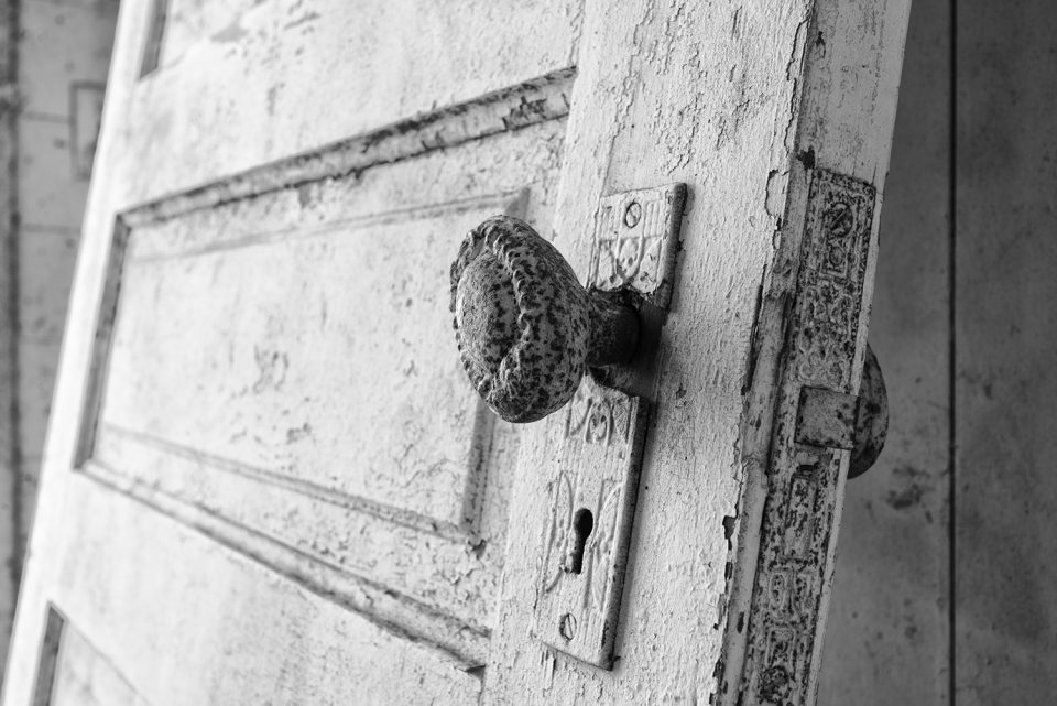 Ornate doorknob on a leaning door in an abandoned farmhouse. Black and white photograph by Keith Dotson.