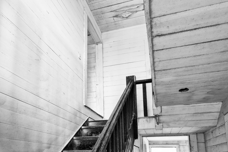 Looking upstairs in an empty old farmhouse. Black and white photograph by Keith Dotson.
