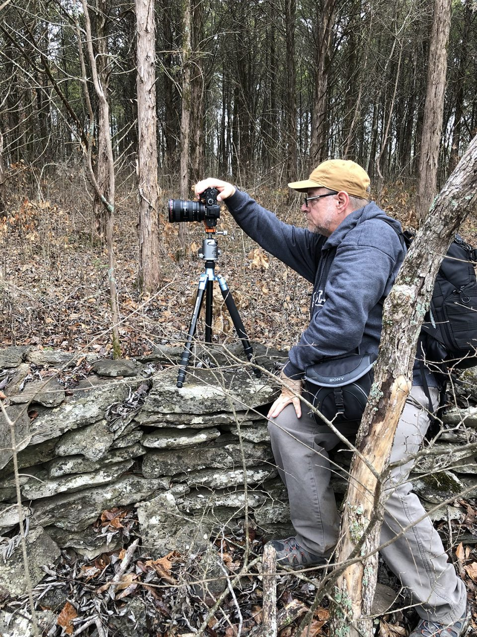 Portrait of photographer Keith Dotson capturing images of the mysterious old stone wall that snakes through the Middle Tennessee woods.
