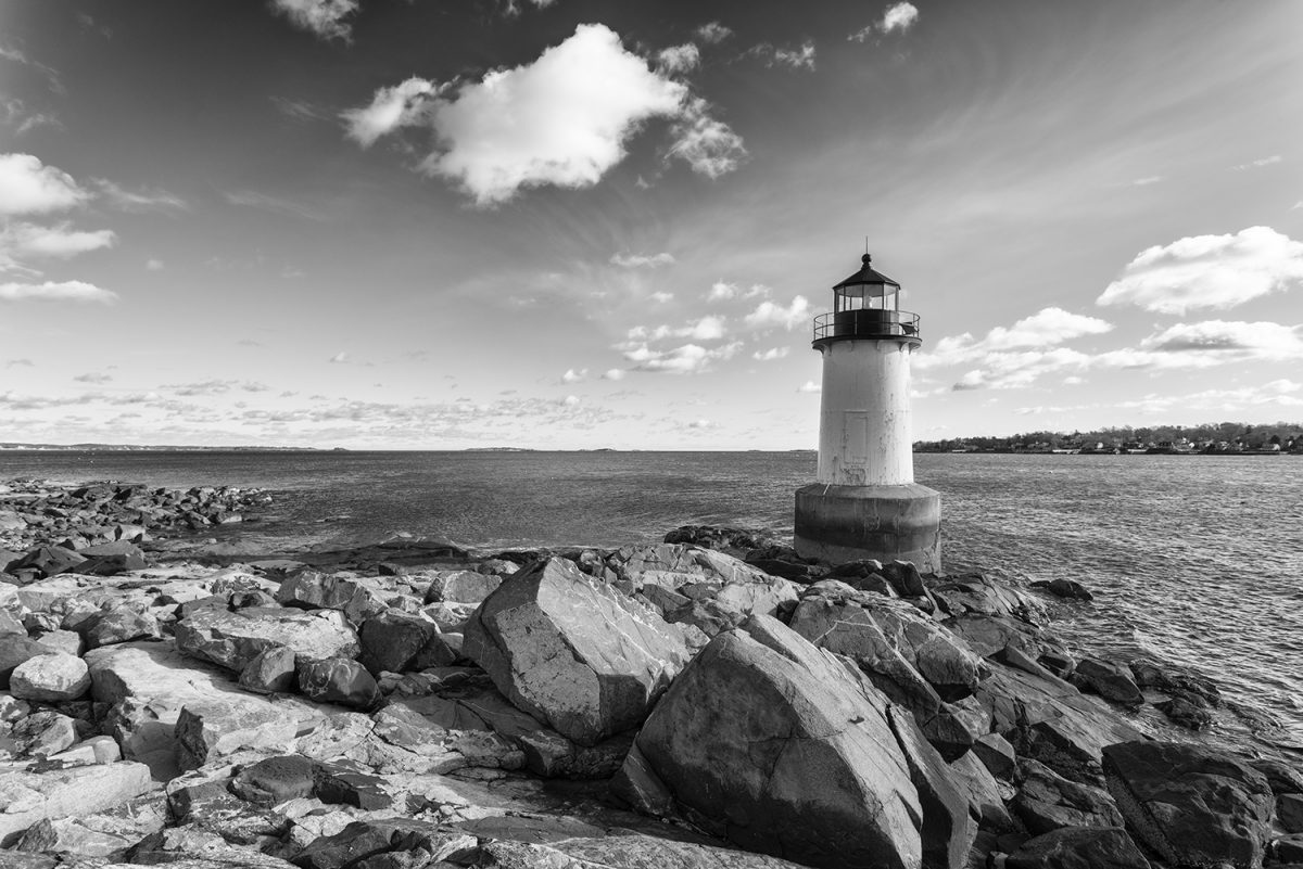 Black and white photograph of the Fort Pickering lighthouse on the rocku coast of Winter Island.