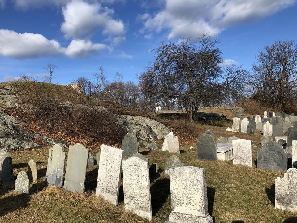 A photograph of the same location at Old Burial Hill taken in 2020. At center left is the leaning white headstone of Mary Doak, visible in the screen shot from the film. In the far distance at left are two matching white tombstones.