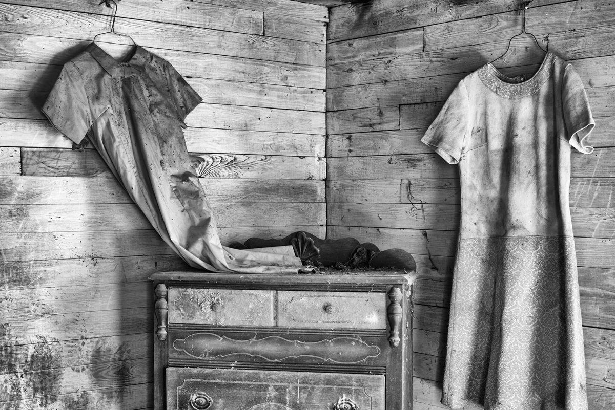 Black and white photograph of old dresses hanging inside an abandoned house. Image by Keith Dotson.