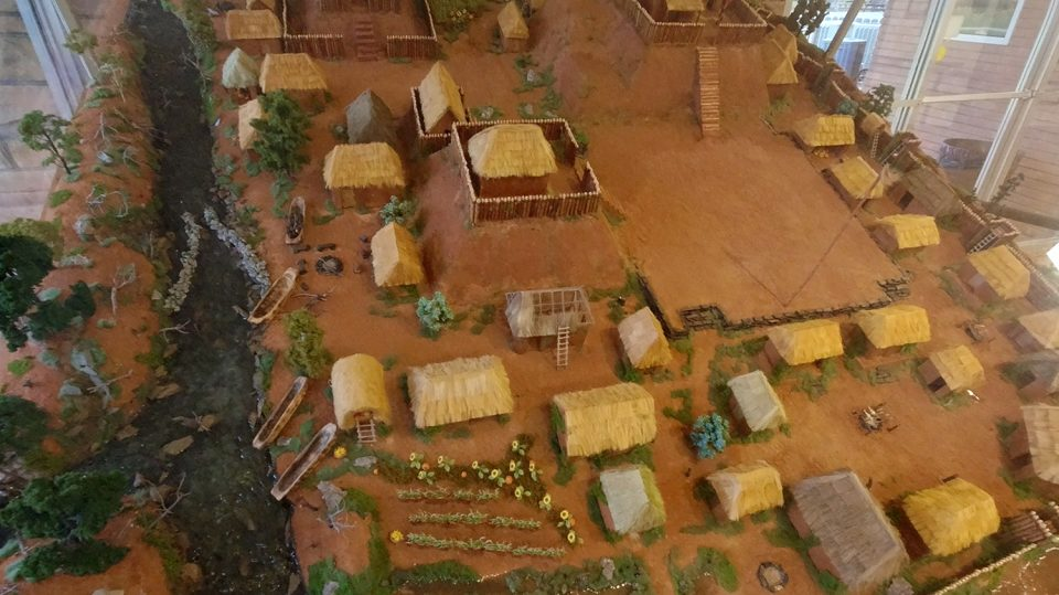 A model of the village at Etowah in the museum shows the river at left, with fish dam. The plaza is visible top-right just below the large mound. At bottom and far-right, portions of the wooden palisade can be seen.