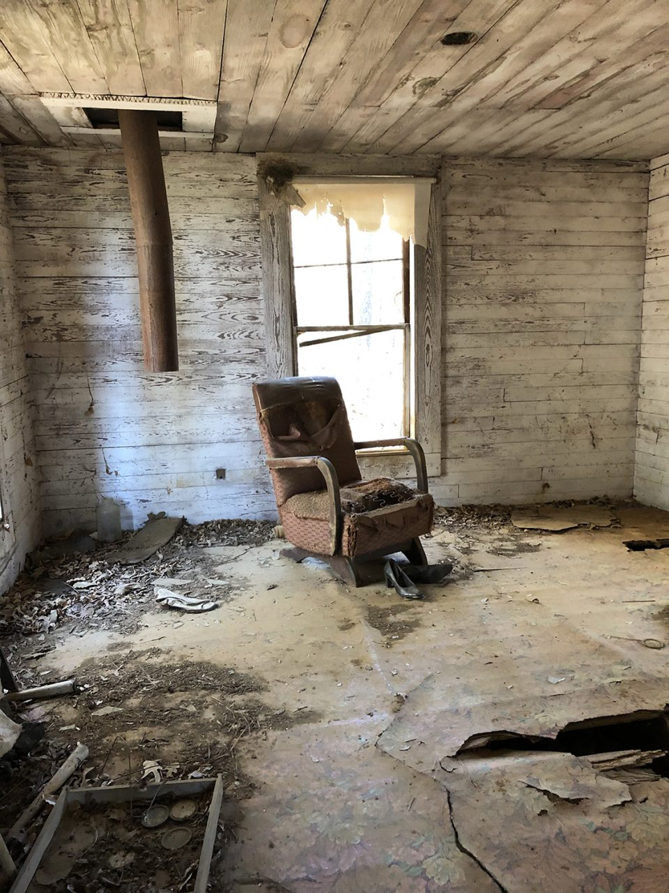 The old chair has women's shoes in front of it, which were probably placed by a previous visitor. The stove pipe remains even though the stove is long gone. All that remains of the window shade are tatters blowing in the breeze.