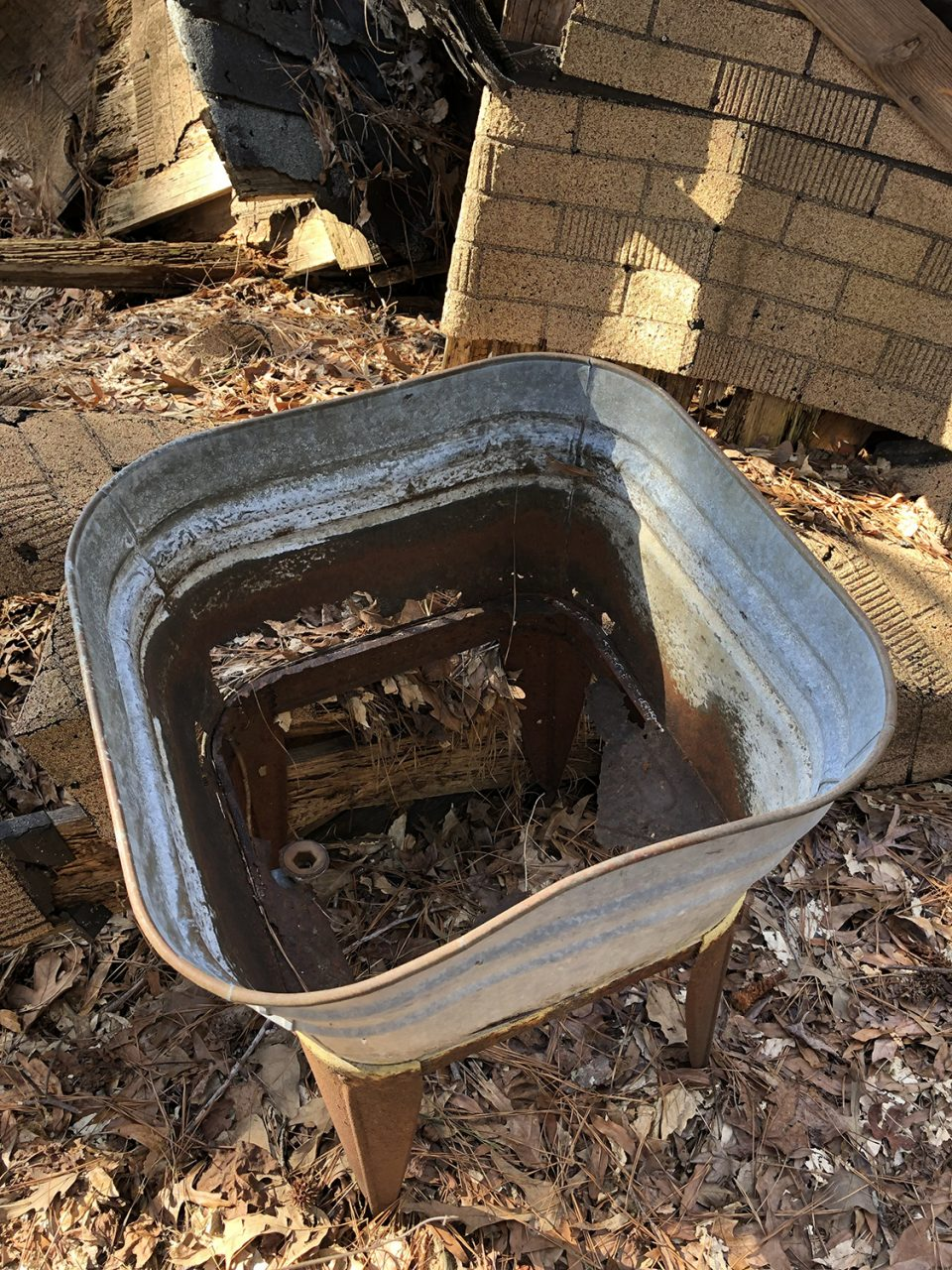 A rusty wash bucket in the yard near the partially collapsed roof.