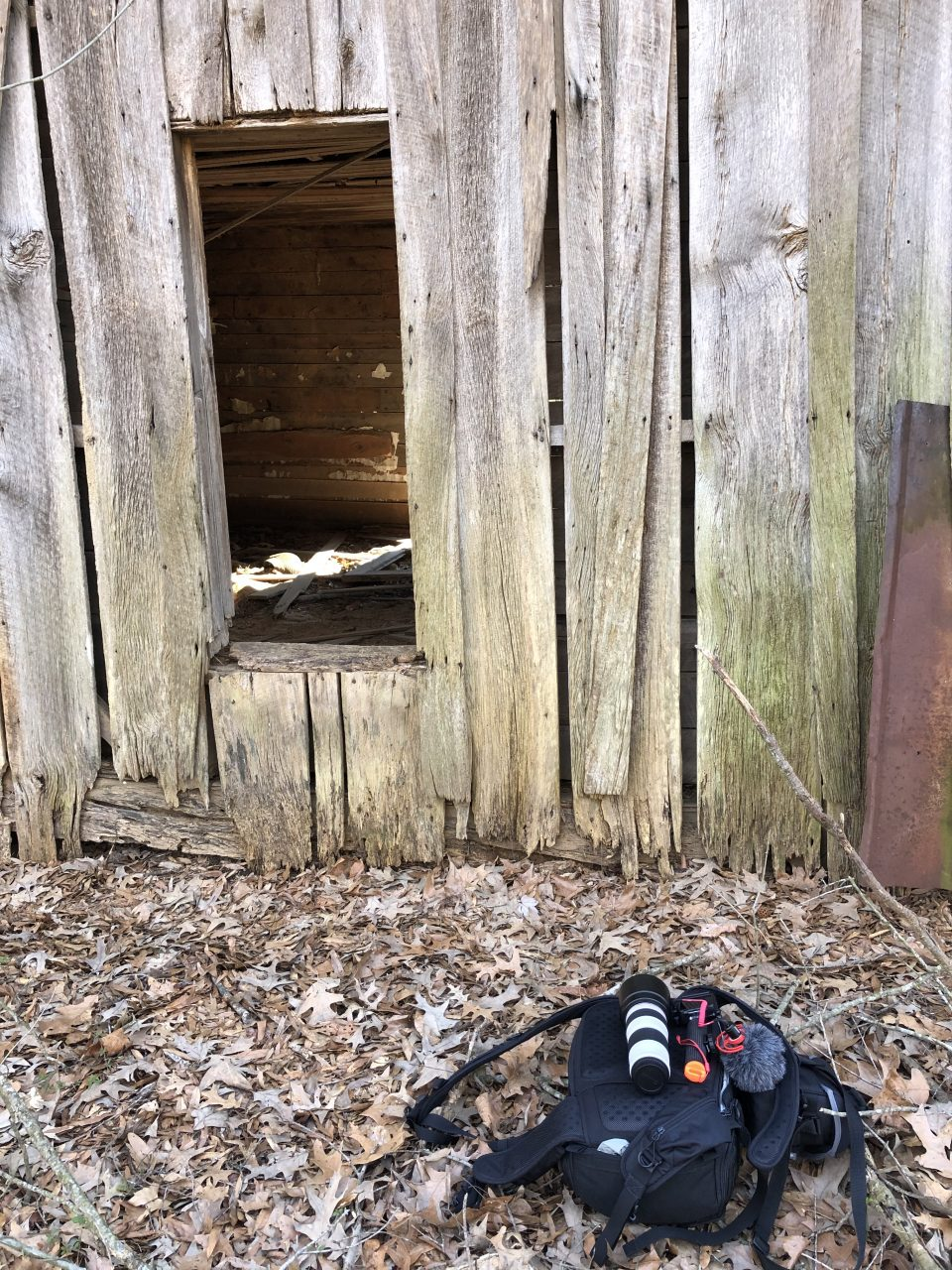 photograph of Keith Dotson's camera bag lying on the ground behind an abandoned farm house.