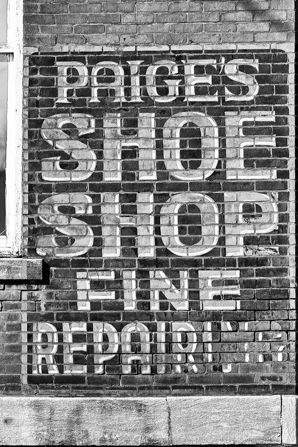 Fading sign for a long-gone shoe shop. Black and white photograph by Keith Dotson.