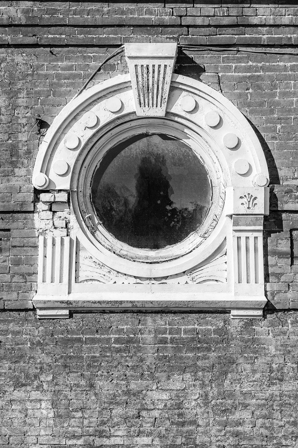 A porthole style window on a large building now demolished. Black and white photograph by Keith Dotson.