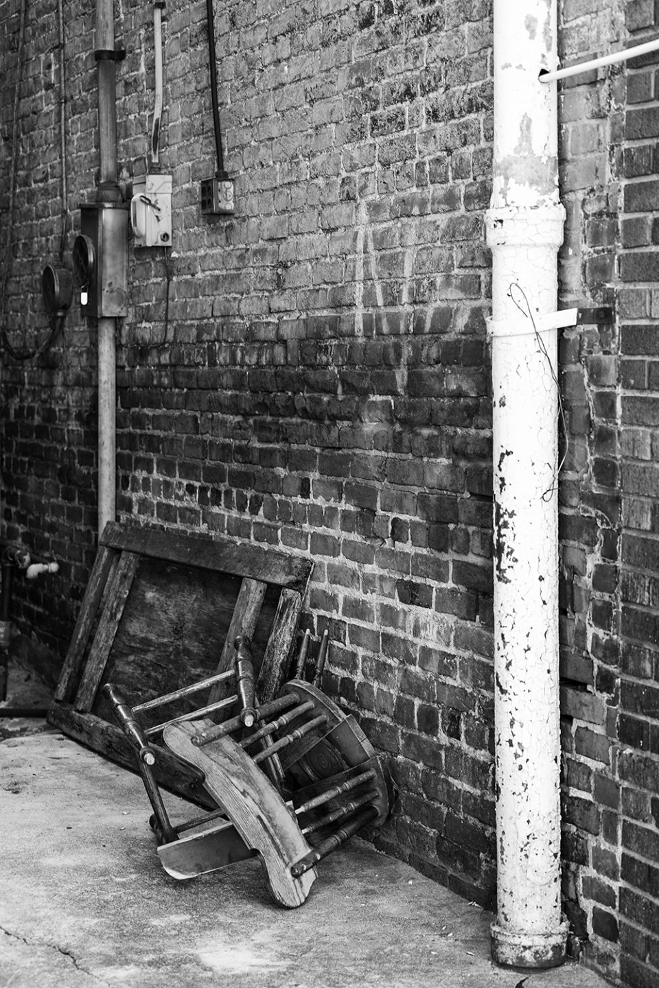Broken chair in a Hopkinsville alley. Black and white photograph by Keith Dotson.