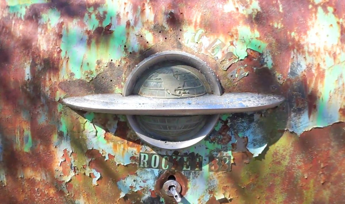 Chrome ornament on the back of a rusty old Rocket 88 automobile