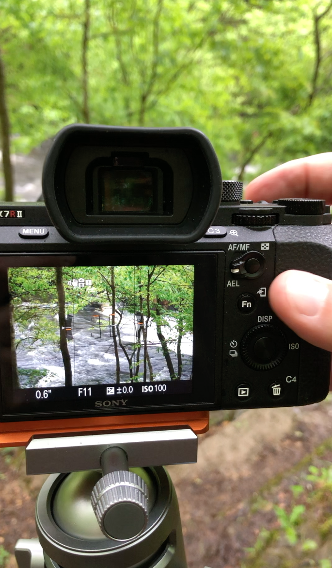 Framing up a shot of the river rushing in a blur behind a few trees on the ledge above.