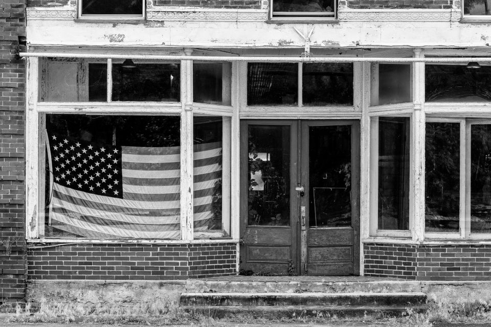 Flag in the window of a vacant storefront on Main Street in Pamplin City, Virginia. Black and white photograph by Keith Dotson.