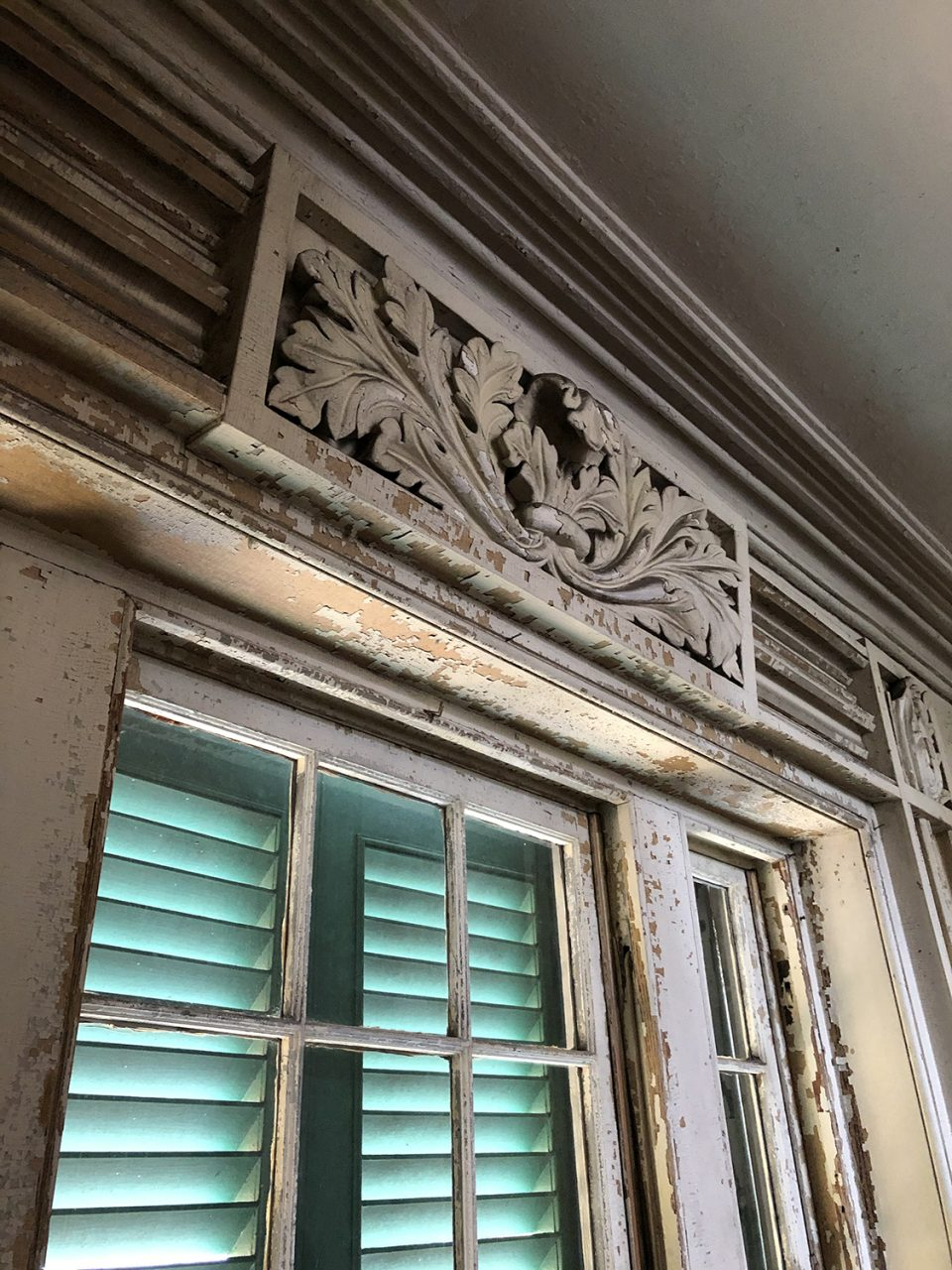 Ornate plaster details over the window inside a big southern mansion in Charleston