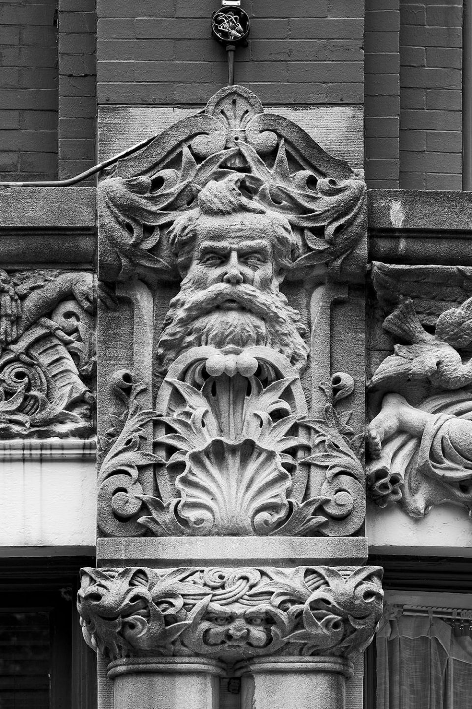 Black and white photograph by Keith Dotson of Cyrus T.C. Deake seen as a stone carving on the exterior of the Drhumore Building in Asheville, North Carolina.