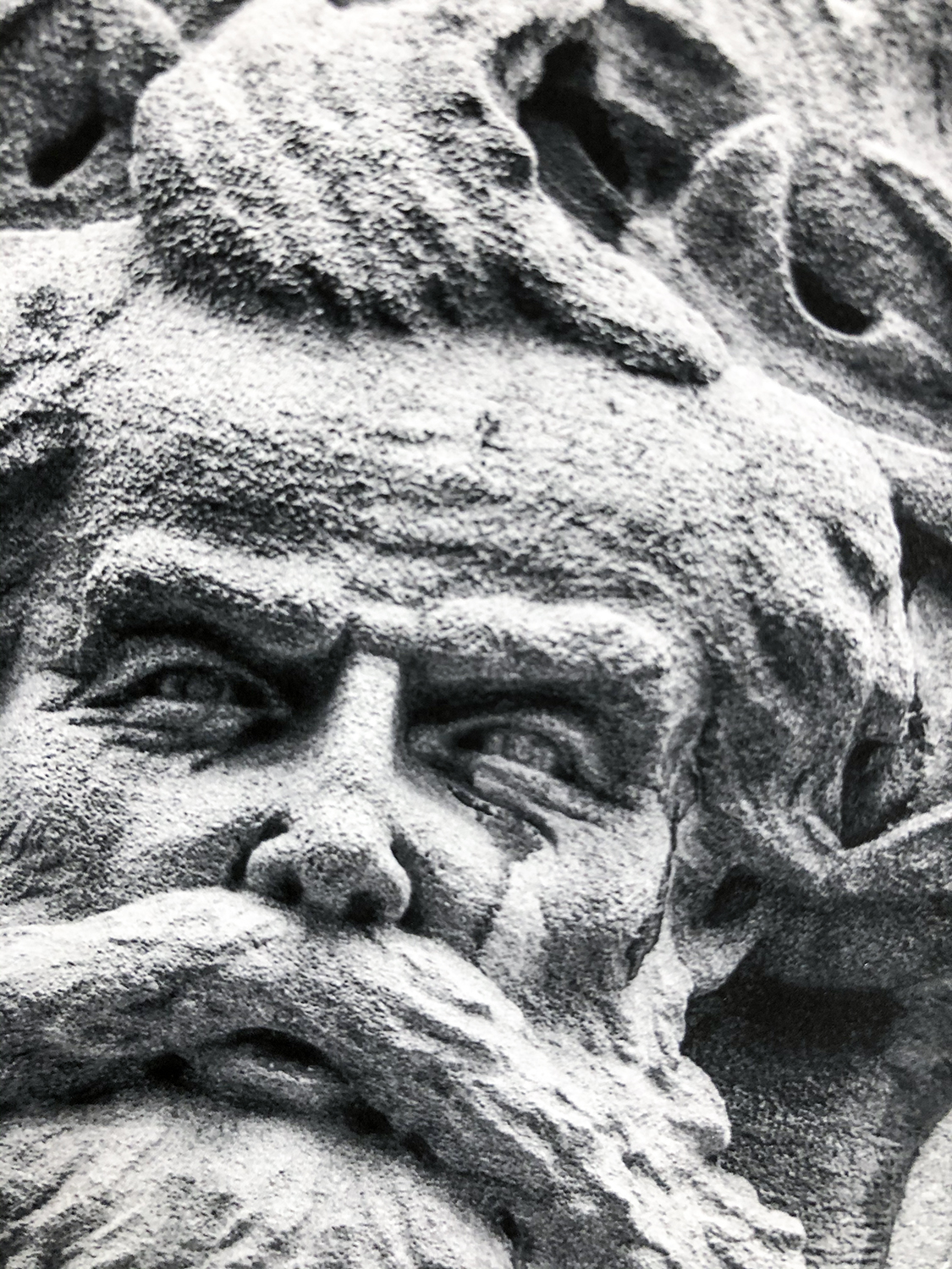 Close-up look at a photographic print of a historic stone relief sculpture on the Drhumor Building in Asheville. This face is likely modelled after a real local citizen, florist Cyrus T. C. Deake.
