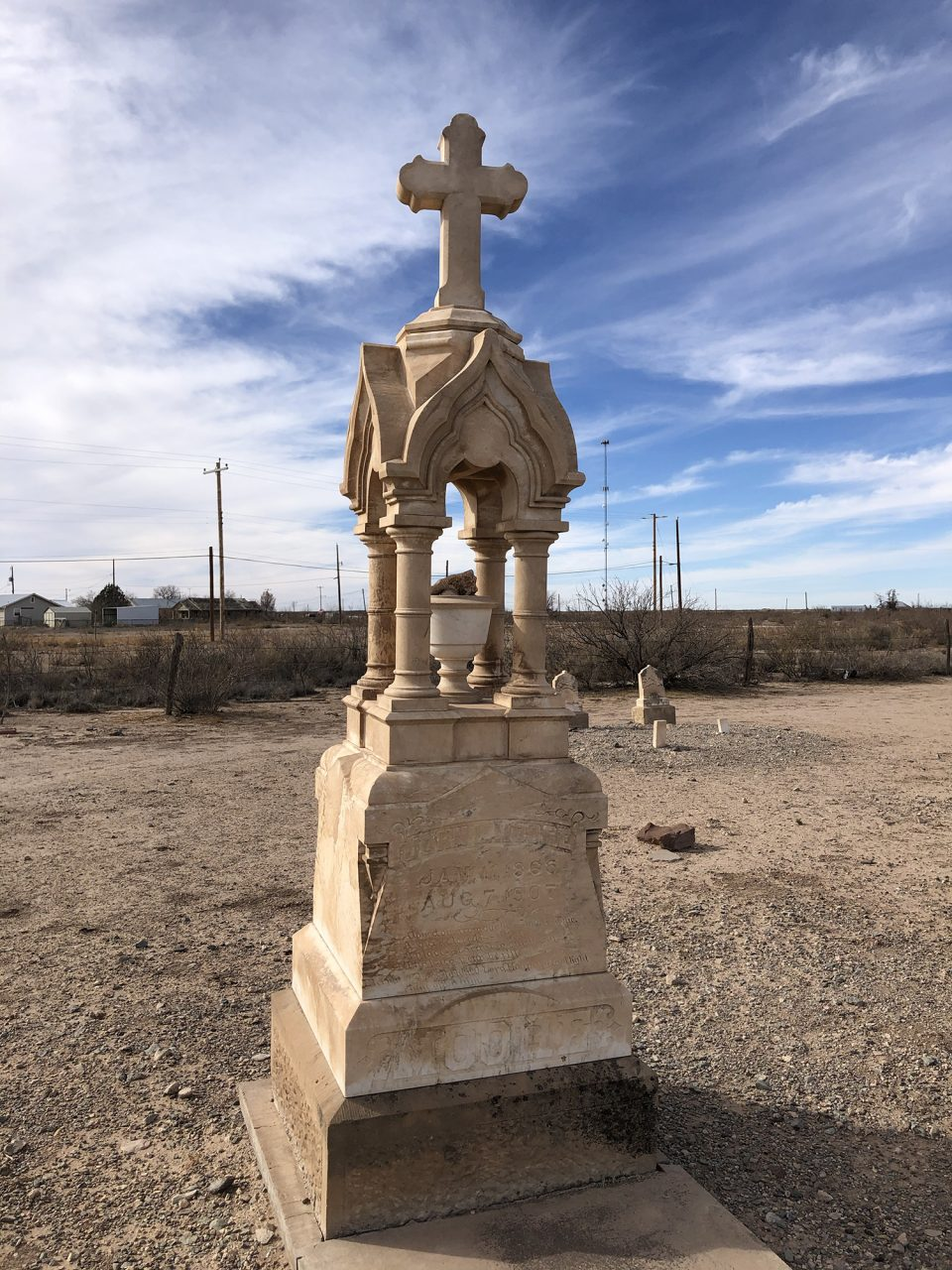 The remarkable stone gravestone of John L. Moore, one of the more elaborate markers in the old windswept cemetery in Toyah, Texas.