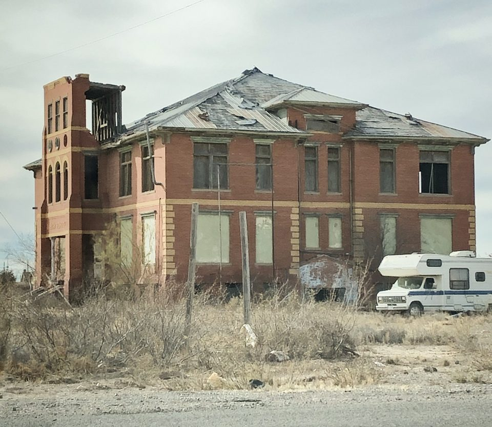 Side view of the abandoned old high school in Toyah, Texas. The RV belongs to a neighboring house.