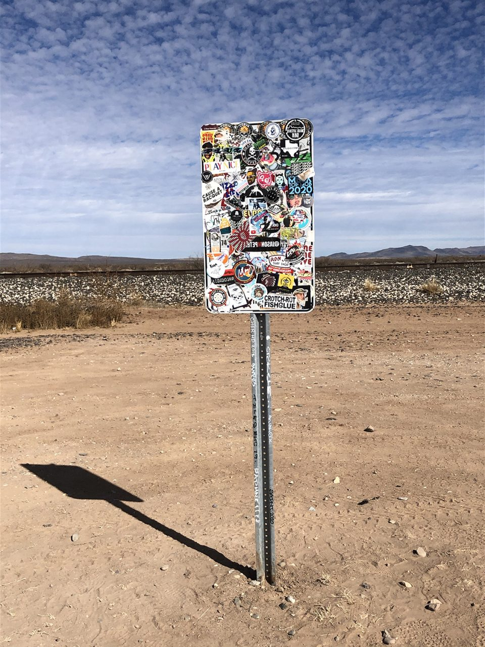 Looking away from Prada Marfa, one sees road signs covered in stickers and graffiti.