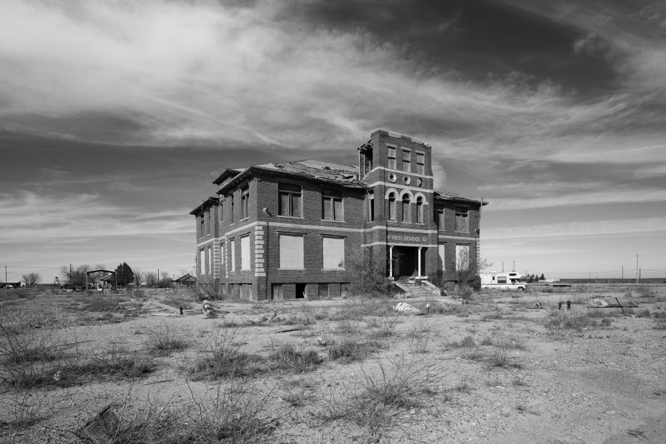 Black and white photograph of an abandoned high school in Toyah, Texas. The decaying structure was built in 1912.