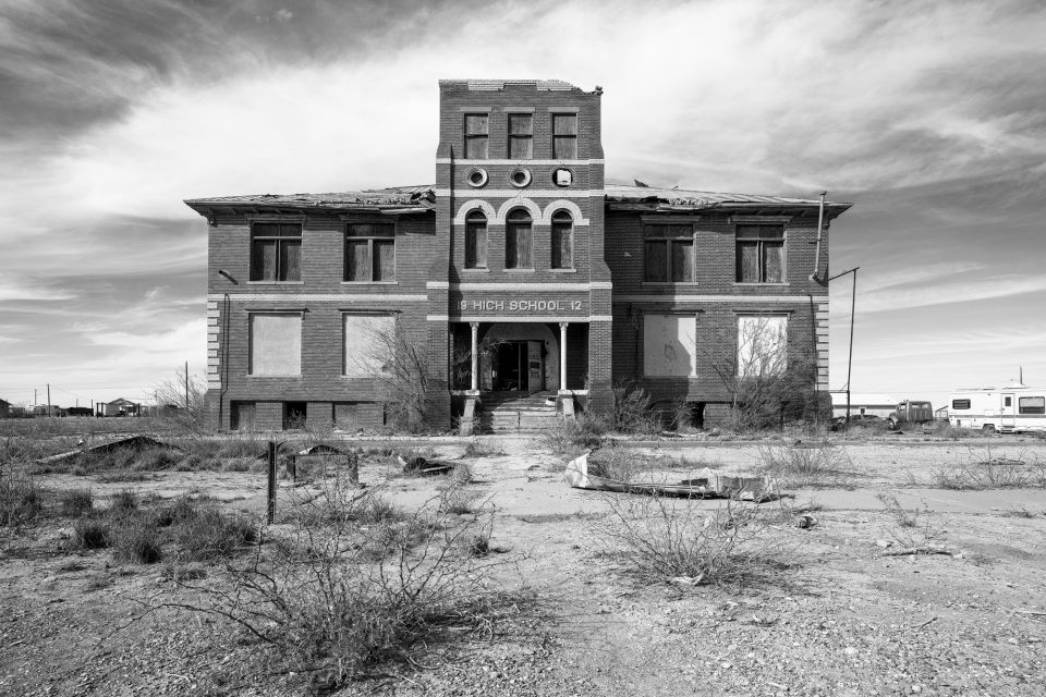 Black and white photograph of an abandoned high school built 1912 in Toyah, Texas. I could hear the roof tin squeaking in the wind, and pigeons cooing in the rafters.