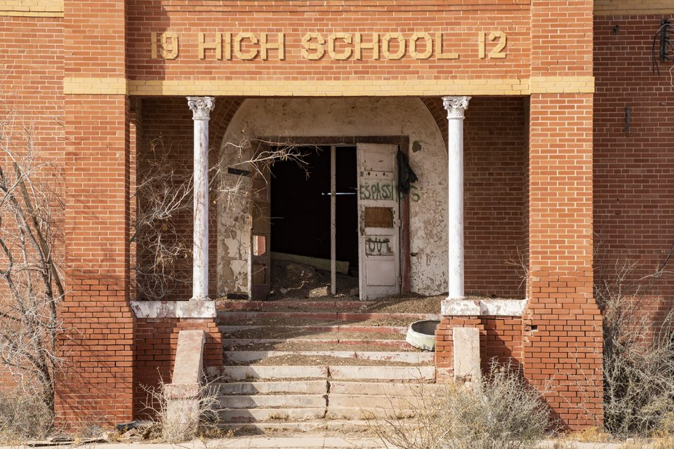 Close-up look at the front entrance of the abandoned high school in Toyah, Texas. A round window casing from above lies on the  steps and mounds of dirt from dust storms are heaped on the steps and inside the open doors.