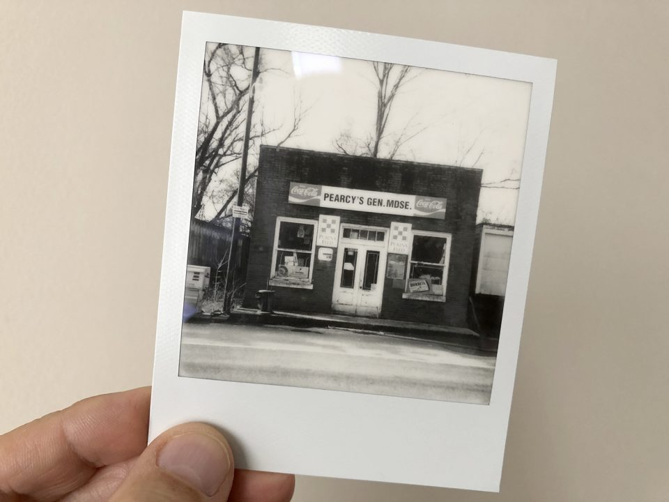 A black and white Polaroid instant print of an old general store, shot on SX-70 film using a vintage polaroid SuperColor Autofocus 3500 camera.