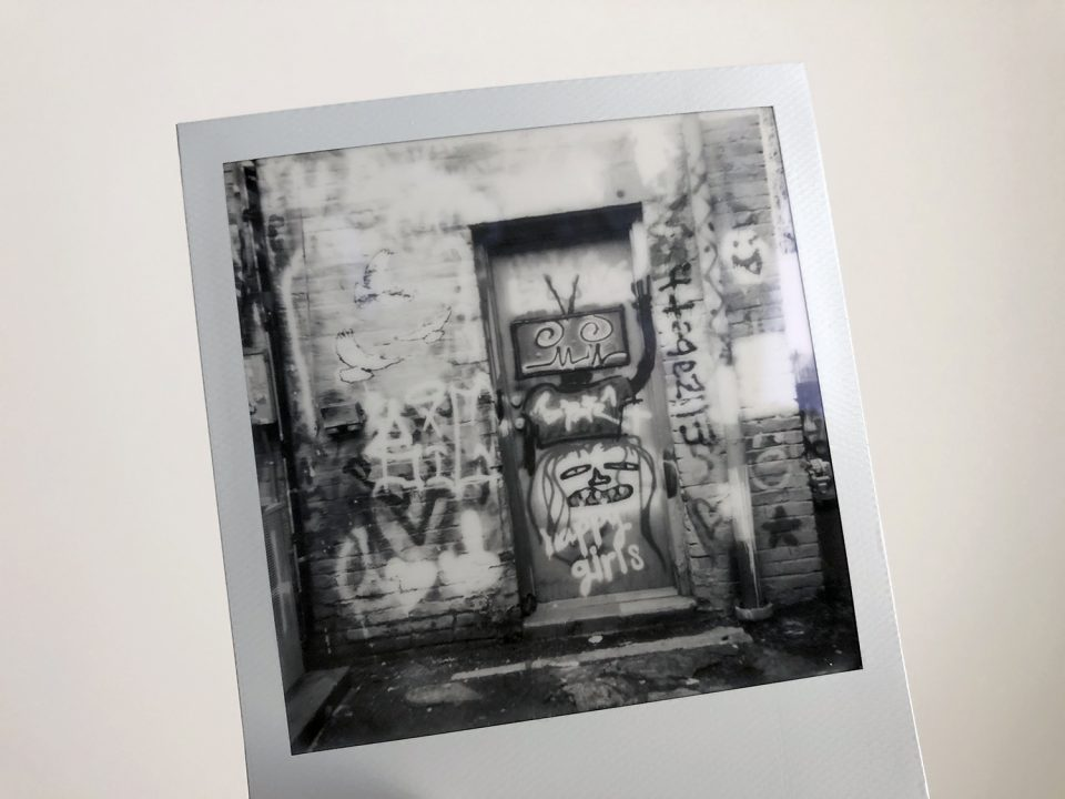 Black and white Polaroid photograph of graffiti in an alley, shot on SX-70 instant film. Photo by Keith Dotson.